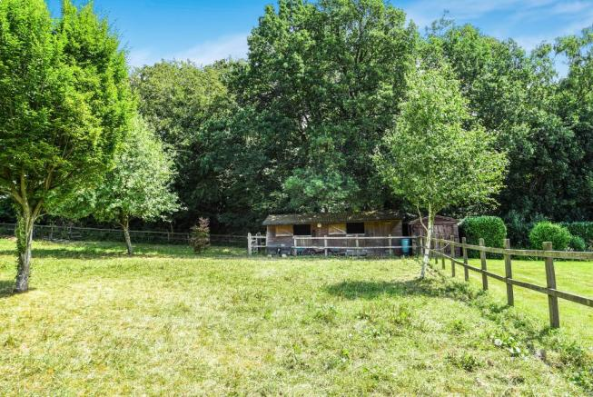 Views across paddock to stables and yard