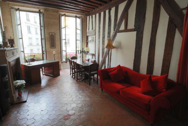 Living room exposed wood beams tiled floor Rue Frederic Sauton Paris