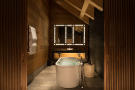 Bathroom free standing bath tub twin sink stone floor Andermatt Chedi Residences
