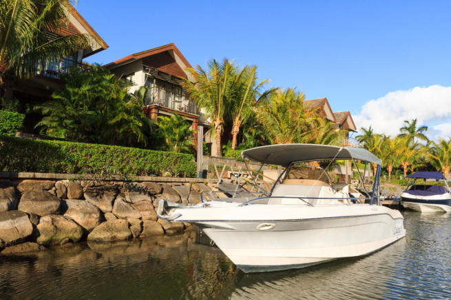 Private boat mooring outside homes at La Balise Marina in Mauritius