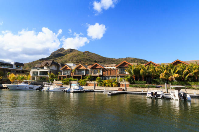 Yacht berths outside homes at La Balise Marina in Mauritius