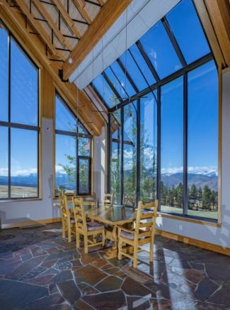 Dining room with double height windows of Montana ranch overlooking valley