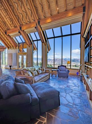 TV lounge with double height windows overlooking valley