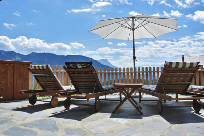 Terrace with sun loungers and parasols at Chalet Alina