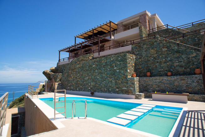Swimming pool and exterior of villa overlooking bay and sea