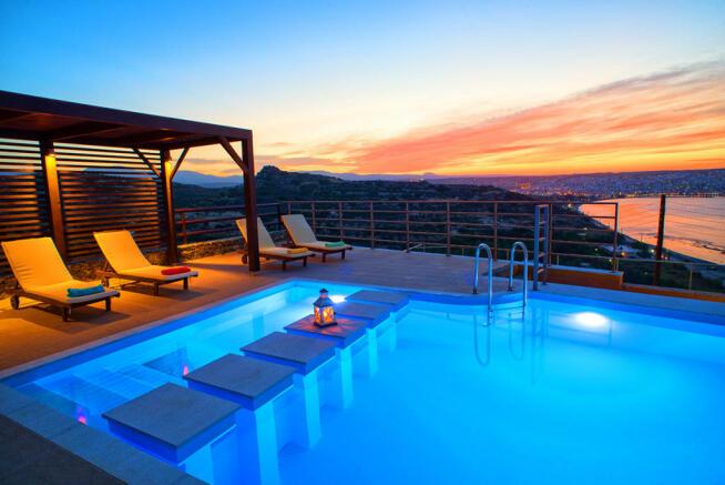 Pool and sunbathing terrace at dusk