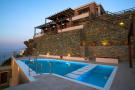Exterior facade of villa with pool and sea views early evening