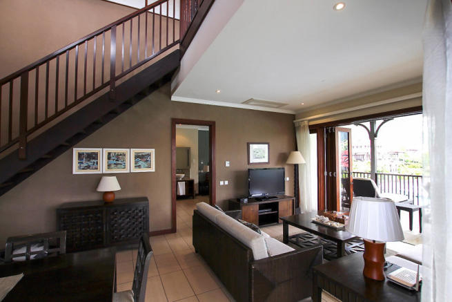 Sitting room facing balcony with stairs to third floor level