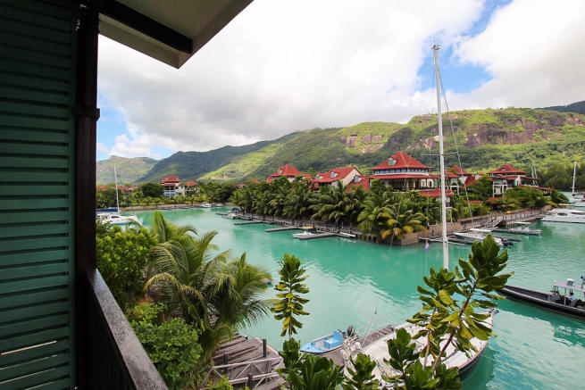 Balcony view over marina, boats and hills of Mahé