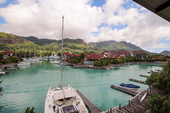 Balcony view over marina, yachts and hills of Mahé