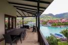 Corner balcony view over marina, boats and hills of Mahé