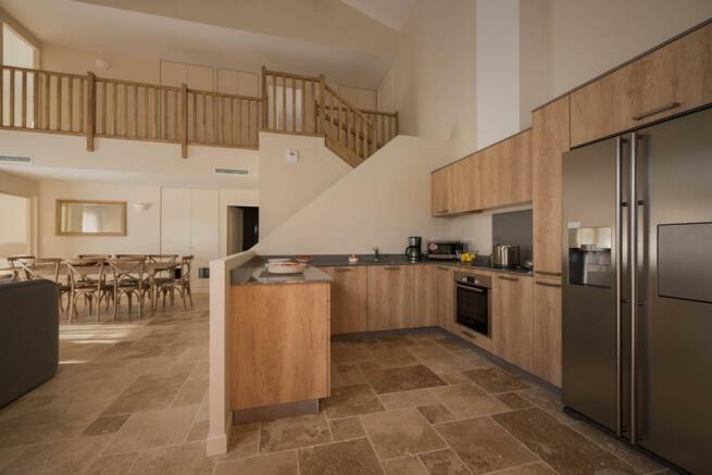 Kitchen with open stairwell behind Wide
