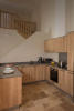 Kitchen with open stairwell behind Tight