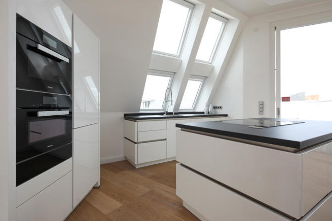 Fitted kitchen with island and access to balcony