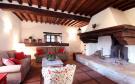 Living room sitting fireplace tiled floor exposed beams Tenuta Cipressino Tuscany