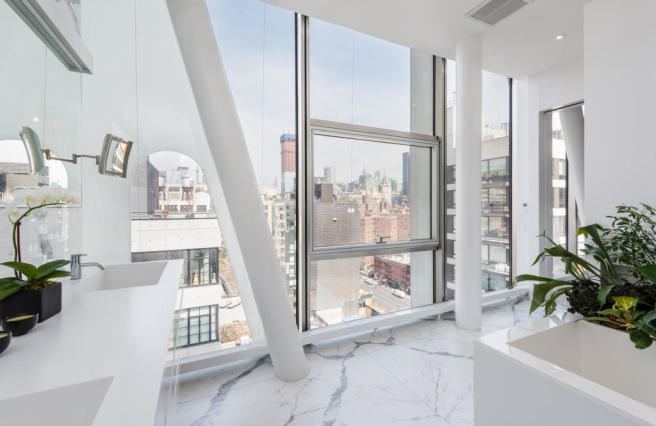 Modern bathroom with marble floor and city views