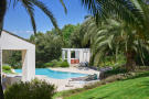 View through palm trees of swimming pool and pool house with Jacuzzi of 5-bed villa in Mougins