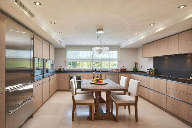 Wide angle shot of the spacious kitchen with Gaggenau appliances throughout in 5-bed villa in Mougins