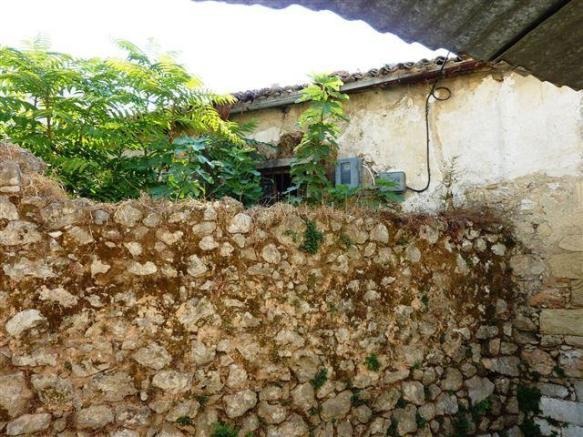 olive press and garden behind wall